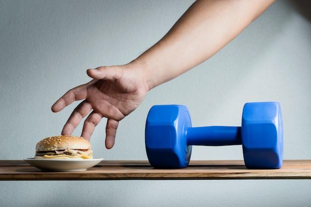 Die männliche hand, die erreicht wird, um burgeridee aufzuheben, trainiert für gewichtsverlustdiätkonzept.