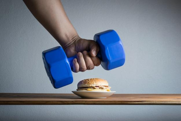 Die männliche hand, die erreicht wird, um dummkopfidee übungen für gewichtsverlustdiätkonzept aufzuheben.