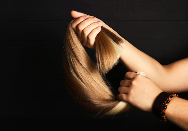 Die männliche hand hält haarsträhnen zur verlängerung.verschiedene haartypen.blonde, rote und braunhaarige abschnitte.haarverlängerungskonzept.