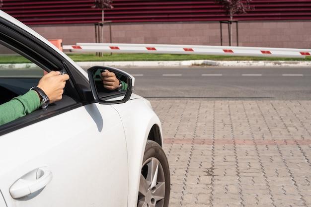 Die männliche hand mit der fernbedienung öffnet eine barriere aus dem inneren des autos