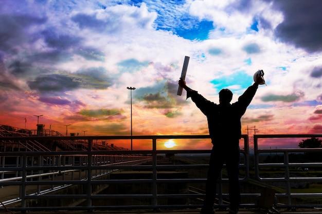 Die männliche silhouette eines männlichen ingenieurs begeistert durch die check-in-zeit bei sonnenuntergang.