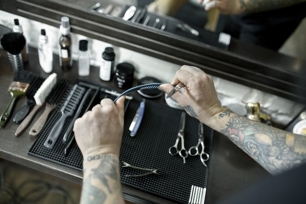 Die männlichen hände und werkzeuge zum bartschneiden im friseursalon.