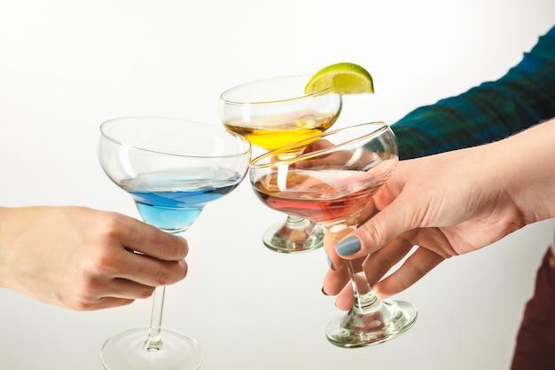 Die männlichen und weiblichen hände mit exotischen cocktails