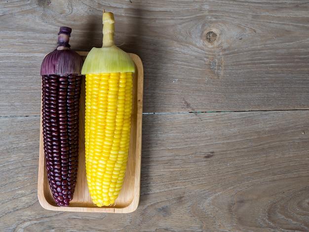 Die maisstiele gekocht und köstlich auf dem hölzernen teller und dem teller auf holztisch.
