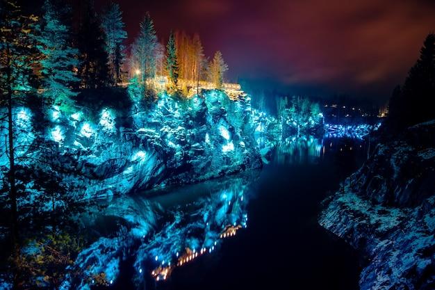 Die majestätische marmorschlucht in ruskeala. schöne farbige beleuchtung. russland, karelien, winternacht.