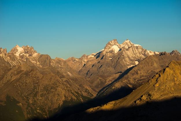 Die majestätischen gipfel des nationalparks massif des ecrins (4101 m) mit den gletschern in frankreich. teleaufnahmeansicht von entferntem bei sonnenaufgang. klarer himmel, herbstfarben.
