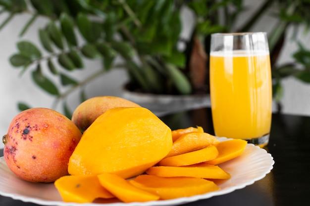 Die mango ist eine frucht unterschiedlicher farbe, die im süden und südosten asiens heimisch ist. foto der mango mit einem weißen teller und einem glas mit mangosaft.