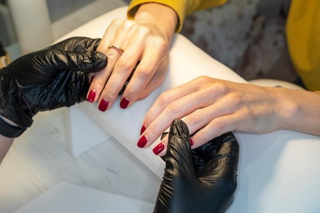 Die maniküre hält die hände des kunden im schönheitssalon. maniküre im salon