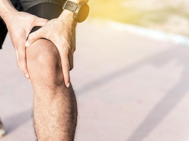 Die manngebrauchshände halten auf seinem knie beim laufen auf straße im park.