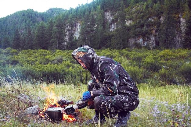 Die manntarnung, die lebensmittel auf lagerfeuer zubereitet, überleben