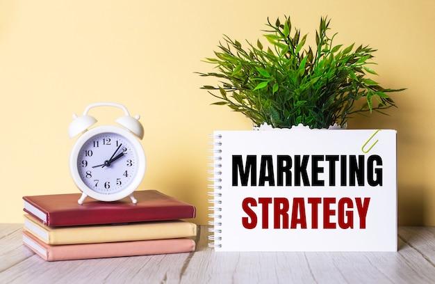Die marketing-strategie steht in einem notizbuch neben einer grünen pflanze und einem weißen wecker, der auf bunten tagebüchern steht