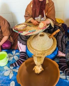Die marokkanerin zeigt argankerne und legt sie in die mühle. essaouira, marokko.