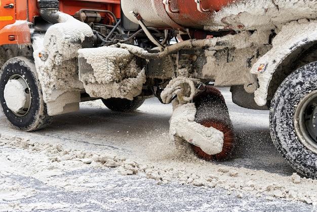 Die maschine mit mechanischer bürste räumt die straße vom schnee. nahaufnahme