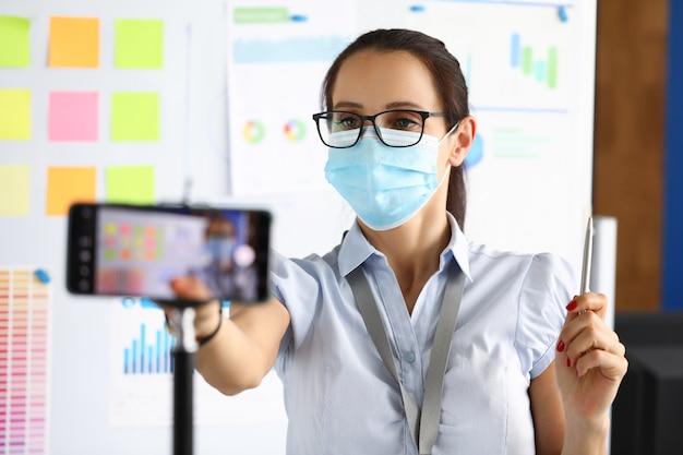Die maskierte geschäftsfrau in einem büro zeichnet die präsentation auf dem smartphone auf
