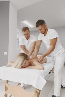 Die massage mit vier händen. konzept der gesundheitsversorgung und der weiblichen schönheit. zwei masseurinnen machen eine doppelmassage eines mädchens. frau in einem spa-salon.