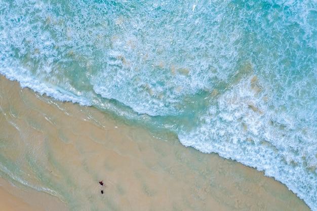 Die meereswelle am strand und touristische luftaufnahme
