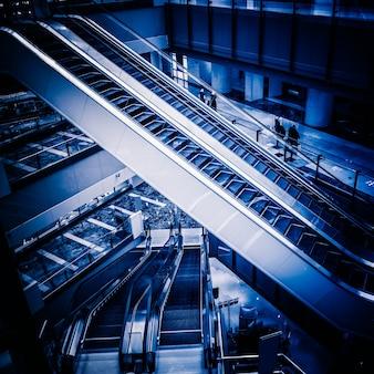 Die mehrfachen schritte und die richtungen einer rolltreppe im modernen einkaufszentrum, schwarzweiss-hintergrund