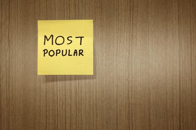 Die meiste populäre handgeschriebene mitteilung auf papieranmerkung über hölzernen hintergrund.