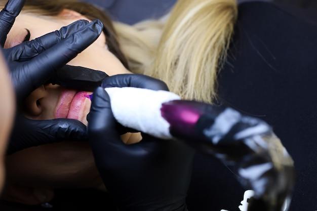 Die meistertätowiererin streckt mit zwei fingern die lippen des models und setzt dann ein tattoo auf ihre lippen