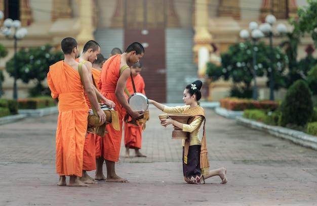 Die menschen geben den buddhistischen mönchen in vientiane, laos, nahrungsmittelopfer.