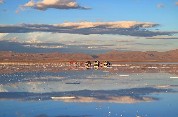 Die menschen genießen die aktivitäten zum spiegeleffekt der salar de uyuni salt flats, bolivien