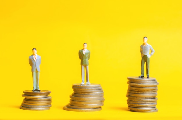 Die menschen stehen auf münzsäulen. das konzept des karrierewachstums, die einzahlungsrate.