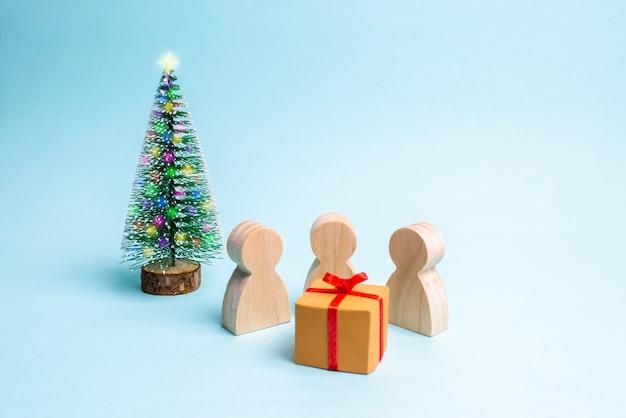 Die menschen versammelten sich um das geschenk und sind bereit, es zu öffnen.
