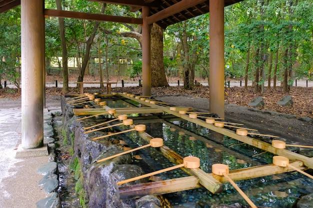 Die menschen verwenden hölzernes schaufelwasser, um den körper zu reinigen, bevor sie den tempel und den schrein besuchen, um ihn anzubeten, was japanische temizuya nennt. traditionelles weihwasser des japanischen wasseramsels.