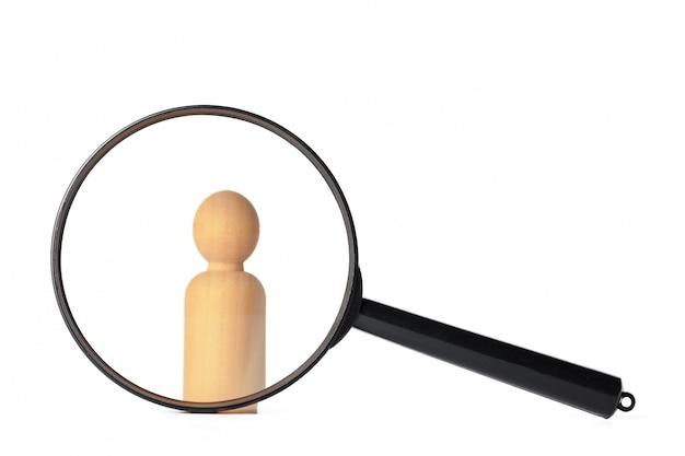 Die menschliche figur steht in der nähe einer lupe. das konzept der suche nach menschen und arbeitnehmern. suche nach freien stellen und arbeit. personalmanagement