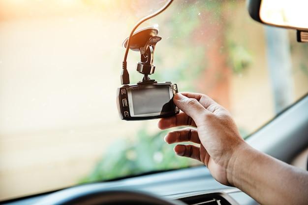 Die menschliche hand berührt die cctv-autokamera, für prüfsystem vor gebrauch