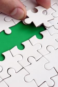 Die menschliche hand ebnet den weg zur oberfläche des puzzles