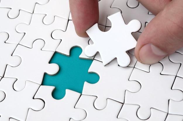 Die menschliche hand füllt die letzten fehlenden elemente der oberfläche aus dem puzzle.