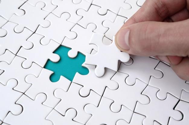 Die menschliche hand füllt die letzten fehlenden elemente der oberfläche aus dem puzzle