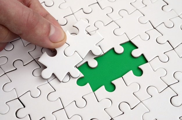 Die menschliche hand füllt die letzten fehlenden elemente der oberfläche des puzzles