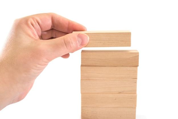 Die menschliche hand legt holzklötze nieder. geschäftsentwicklungskonzept