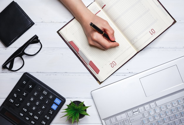 Die menschliche hand schreibt pläne für aktuelle angelegenheiten in das tägliche tagebuch