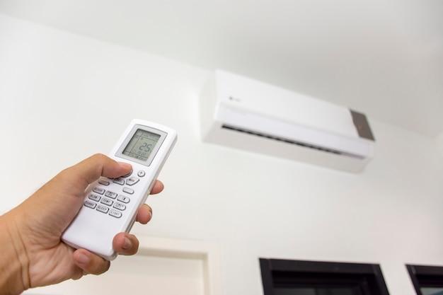 Die menschliche hand verwendet eine weiße fernbedienung der klimaanlage, um die klimaanlage in einem raum einzuschalten und einzustellen.
