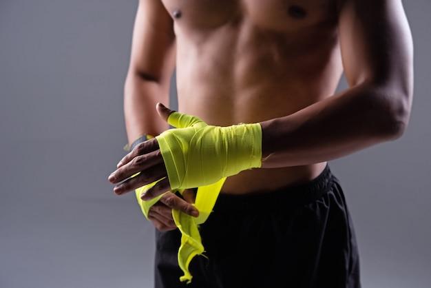 Die menschliche hand wickelte ein gelbes tuch ein, bereitete sich auf das stanzen vor, undeutliches licht