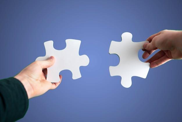 Die menschlichen hände verbinden zwei puzzleteile miteinander, entscheidungsfindung, himmelshintergrund