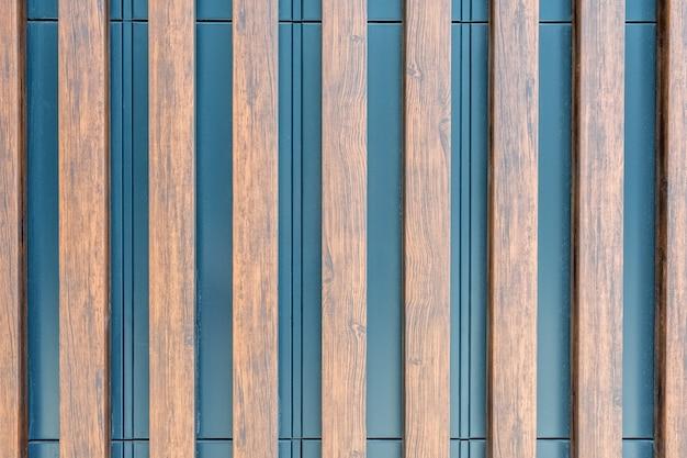 Die metalloberfläche der wand ist mit dekorativen holzlamellen verziert als natürlicher hintergrund