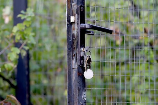 Die metalltür zum garten steht offen und im schloss stecken schlüssel. nahaufnahmefoto.
