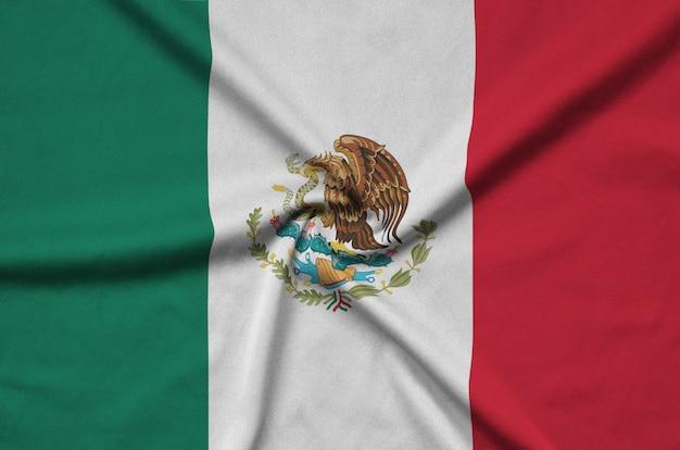 Die mexikanische flagge ist auf einem sportstoff mit vielen falten abgebildet.