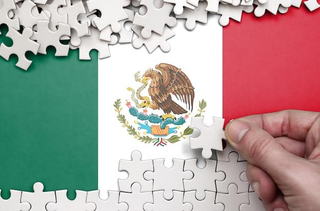 Die mexikanische flagge ist auf einem tisch abgebildet, auf dem die menschliche hand ein puzzle weißer farbe faltet