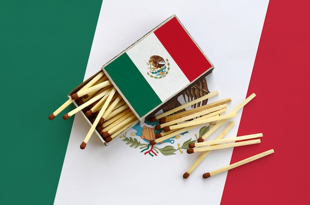 Die mexiko-flagge ist auf einer offenen streichholzschachtel abgebildet, von der mehrere streichhölzer fallen und auf einer großen flagge liegen
