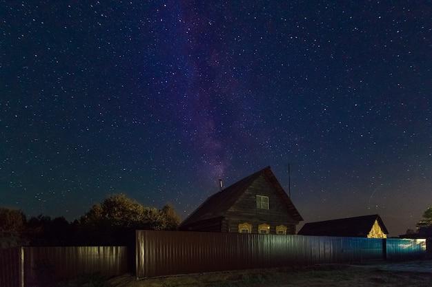 Die milchstraße ein schöner sommernachthimmel im august mit sternen im hintergrund eines dorfhauses