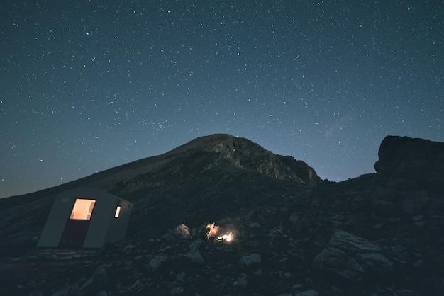 Die milchstraße über den bergen, langzeitbelichtung der italienisch-französischen alpen, berghütte und schutzhütte beleuchtet. getontes bild, weinlesefilter, aufgeteiltes tonen.
