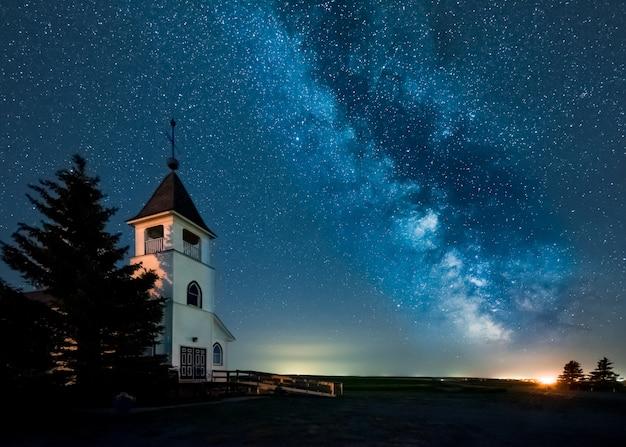 Die milchstraße über einer lutherischen kirche des historischen landes auf den prärien in saskatchewan, kanada