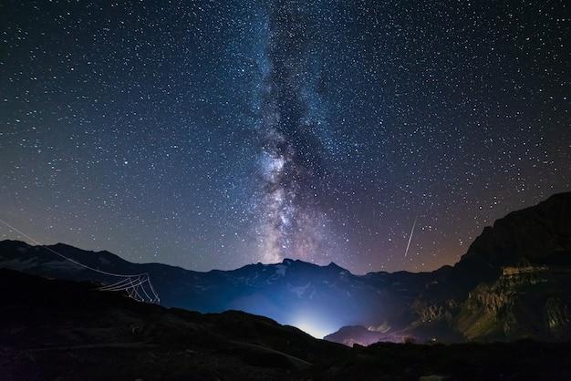 Die milchstraße und sterne über den italienischen französischen alpen. nachthimmel über majestätischen schneebedeckten bergen und gletschern. meteorschauer rechts, jupiterplanet links