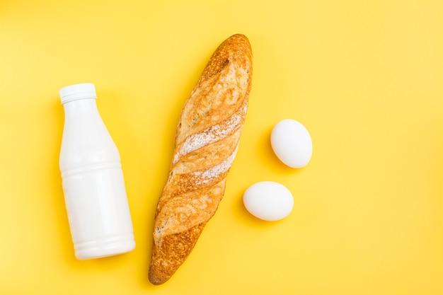 Die mindestmenge an produkten zum frühstück. brot, eier und milch auf gelbem grund