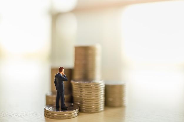 Die miniaturfigur der geschäftsmannfigur steht oben auf dem stapel der münzen